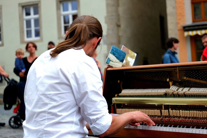 young man at piano outside