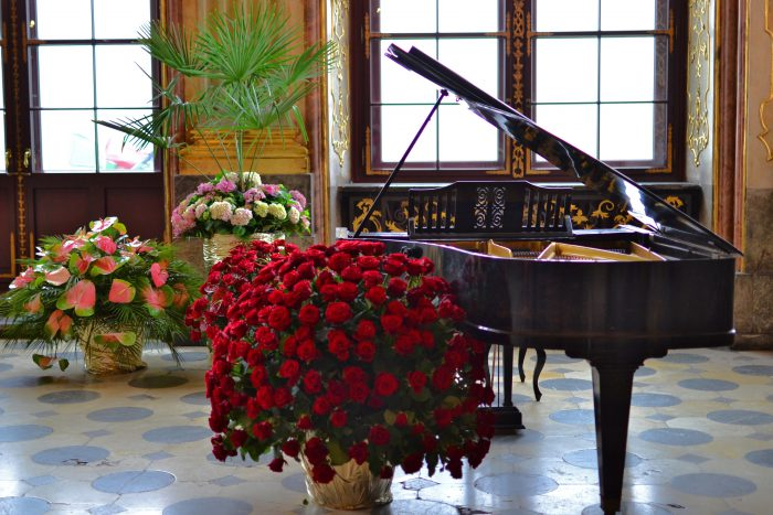 flowers near dark baby grand piano