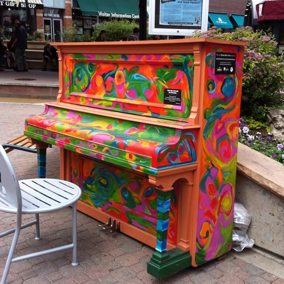 Piano on street covered in art