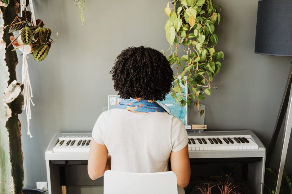 A woman plays her white keyboard near the window