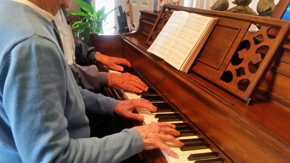 two men at piano with sheet music