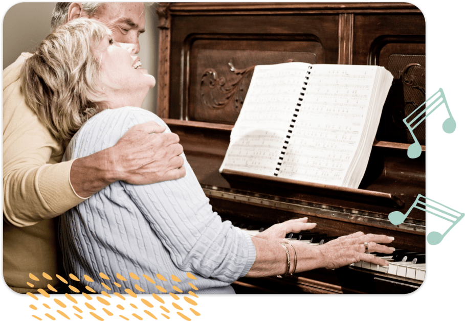Senior man and woman happily play the piano together