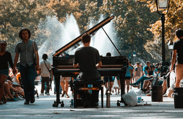 Man playing piano in the middle of a busy park