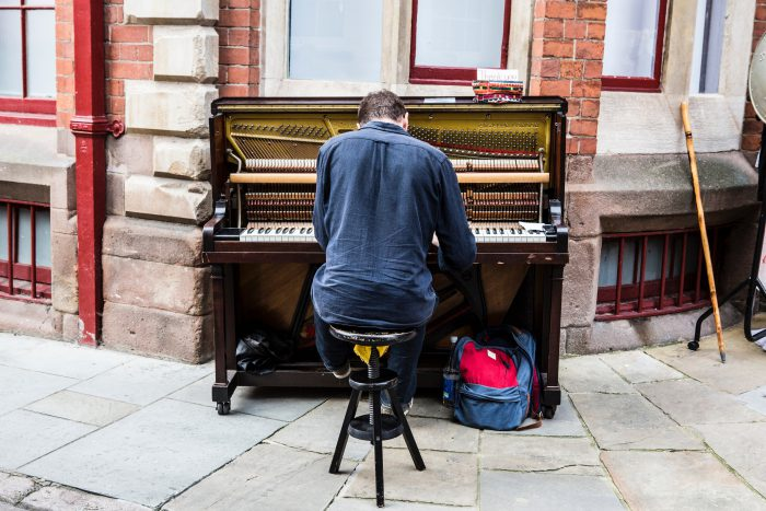 man sitting at piano on sidewalk