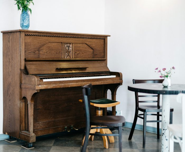 brown upright piano by wall