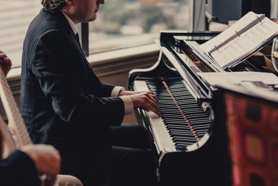 man in suit at piano